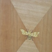 Detail:  Quarter cut cherry door with diamond pattern and inlaid bee, anigre and